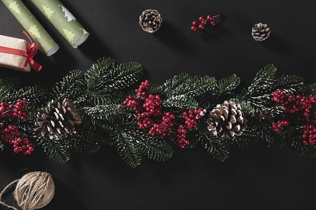 Tiro de vista superior de ramas de pino con cono y regalo sobre un fondo negro