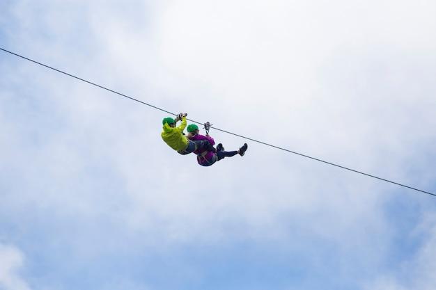 Tirolesa turística aventurera contra el cielo nublado