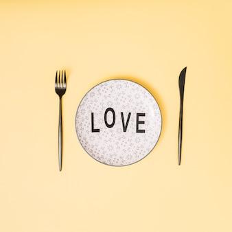 Título de amor en un plato hermoso entre los cubiertos.