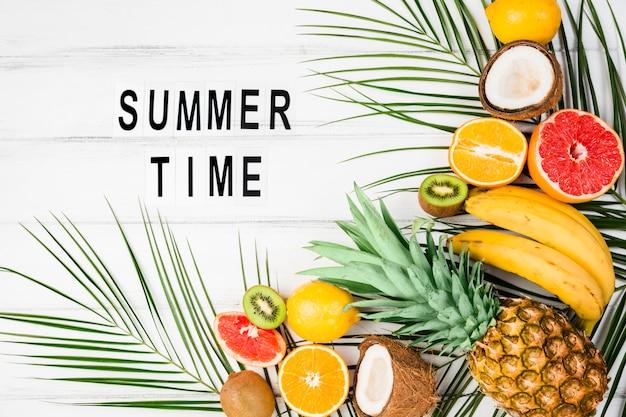 Título de horario de verano entre hojas de plantas cerca de frutas tropicales.