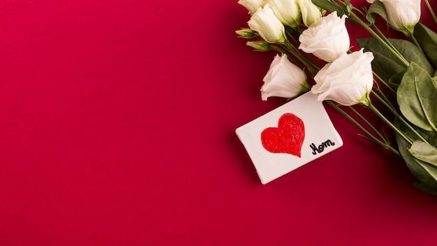 Título de mamá y corazón sobre lienzo cerca de ramo de flores.