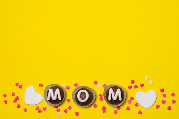 Título de mamá sobre dulces caramelos entre decoraciones.