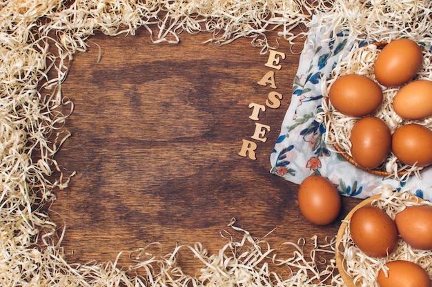 Título de pascua cerca de los huevos de gallina en cuencos sobre material floreado entre la malla a bordo