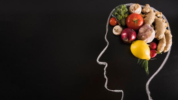 Tiza dibujado cabeza humana con alimentos saludables para el cerebro en la pizarra