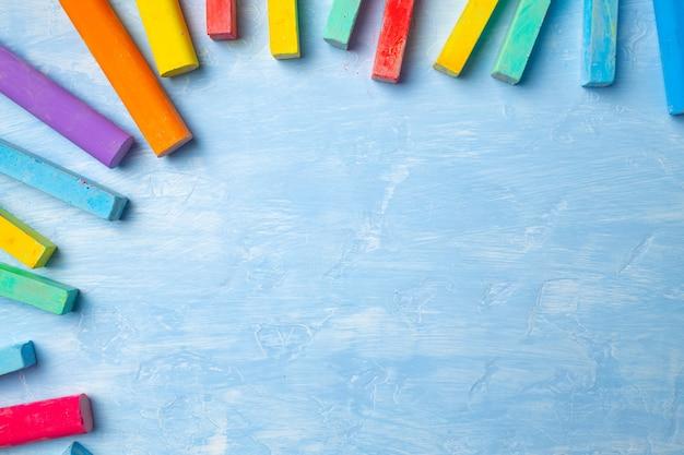 Tizas de colores sobre fondo azul con espacio para copiar texto. concepto de regreso a la escuela