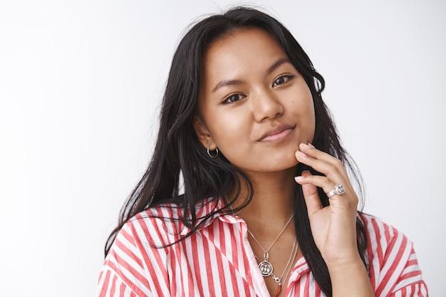 Tnder hermosa y femenina mujer asiática en blusa a rayas inclinando la cabeza suavemente tocando la cara antes de ponerse la máscara facial anti acné sonriendo encantadora y mirando a la cámara sobre una pared blanca