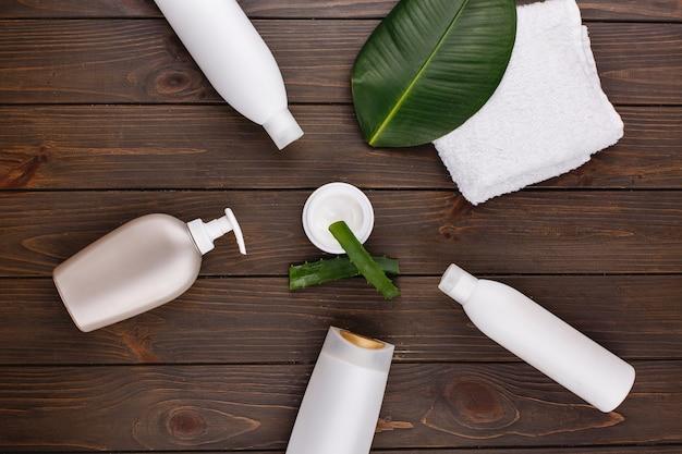 Toalla blanca, botellas de champú y acondicionador en una mesa con hojas verdes y aloe