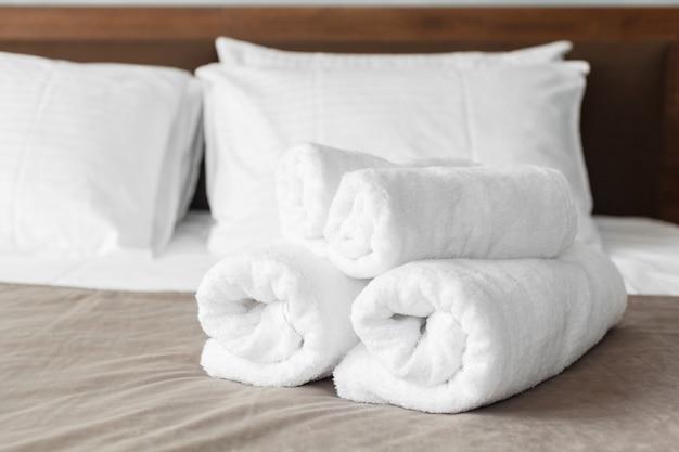 Toalla blanca en la cama en la habitación para el cliente del hotel