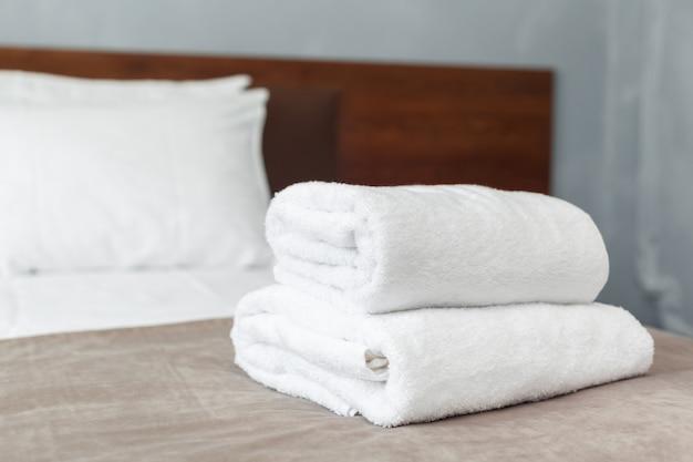 Toalla blanca en cama en habitación de huéspedes para cliente del hotel.