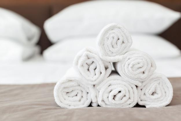 Toalla blanca en la cama en la habitación de huéspedes para el cliente del hotel