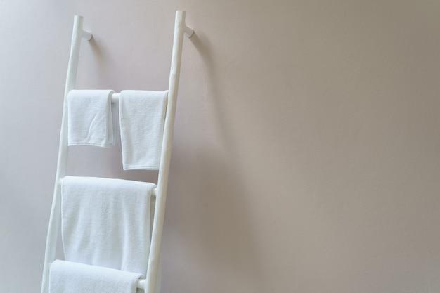 Toalla blanca colgada en las escaleras de madera blanca de pie.