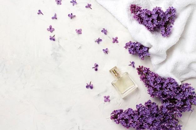 Toalla blanca, frasco de perfume, flores de color lila. vista superior, plano, endecha, copia espacio.