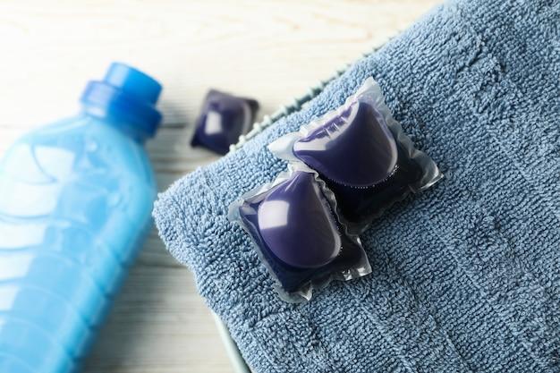 Toalla con cápsulas de lavandería y detergente sobre mesa de madera blanca