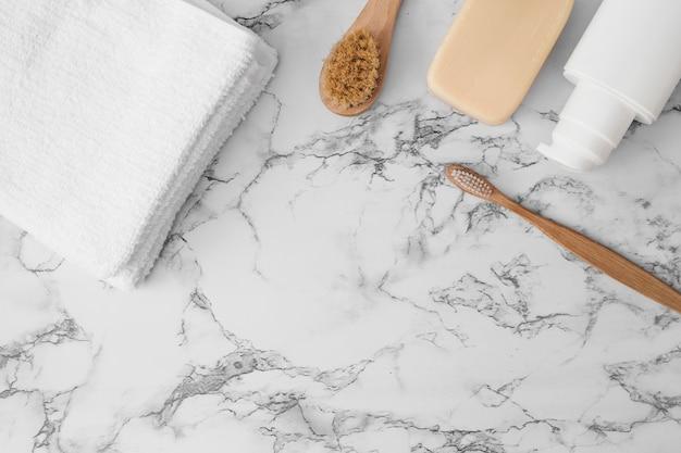 Toalla; cepillo; jabonera y botella cosmética en superficie de mármol.