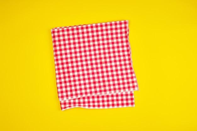 Toalla de cocina a cuadros roja blanca sobre un fondo amarillo