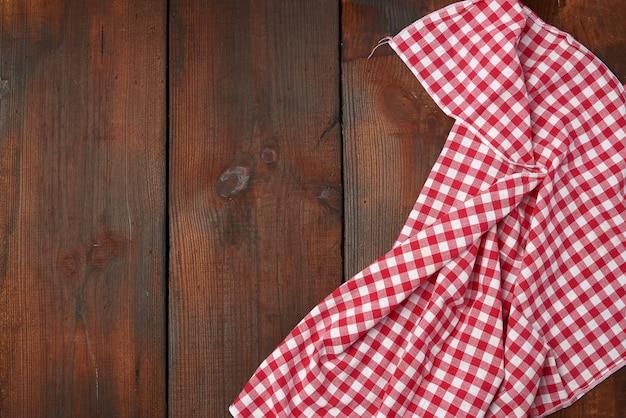 Toalla de cocina a cuadros rojo blanco sobre una madera marrón