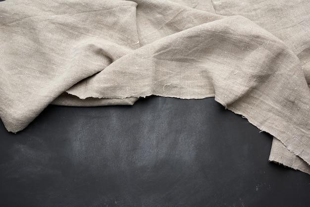Toalla de cocina gris textil doblada sobre una mesa de madera negra, vista superior, espacio vacío.
