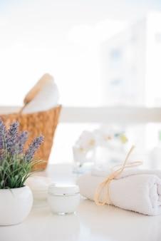Toalla y crema cerca de flores de lavanda en mesa blanca