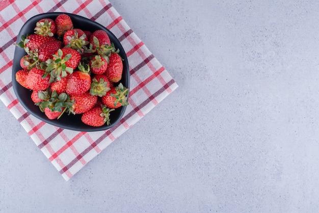 Toalla cuidadosamente doblada debajo de un recipiente con un montón de fresas sobre fondo de mármol. foto de alta calidad