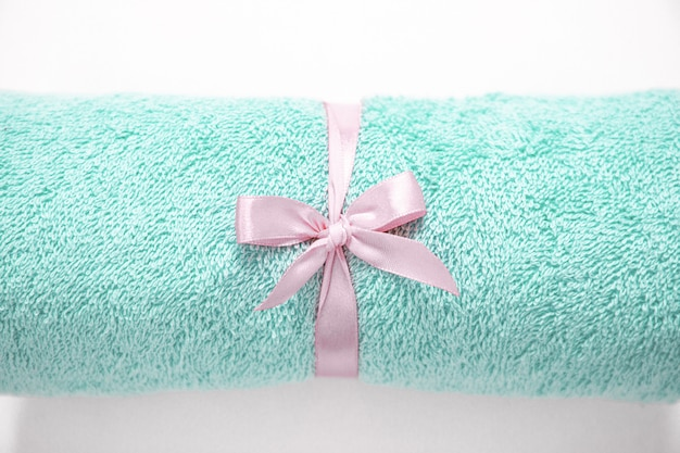 Toalla de felpa enrollada en aguamarina atada por una cinta rosa contra un fondo blanco. vista superior.
