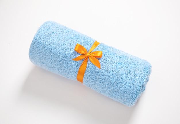 Toalla de felpa enrollada azul atada por cinta naranja sobre un fondo blanco.