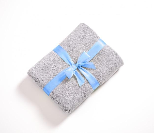 Toalla de felpa gris doblada contra el fondo blanco, toalla apilada y atada por una cinta azul aislada