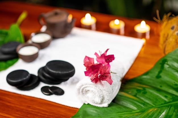 Una toalla de felpa en la que hay una tetera de arcilla y tazas para bebidas con leche, piedras para terapia de piedras, pequeñas velas encendidas, una flor de mangolia y una toalla de felpa retorcida sobre una mesa de madera.