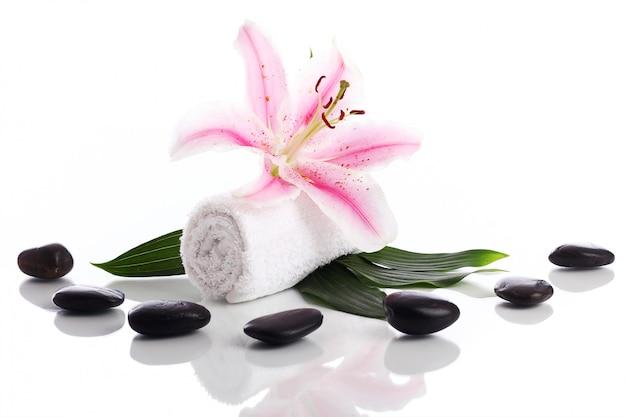 Toalla con flor de lirio y piedras para masaje