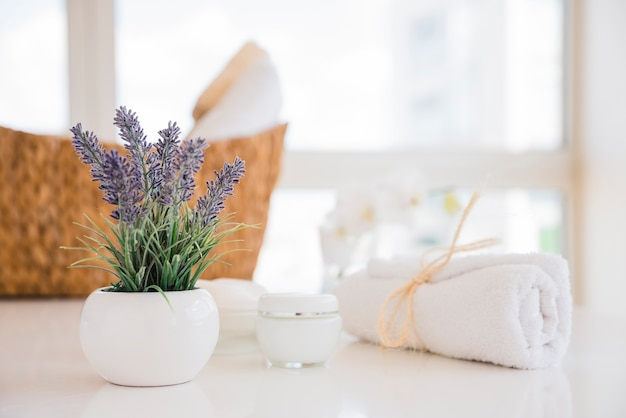 Toalla y flores de lavanda en mesa blanca con crema