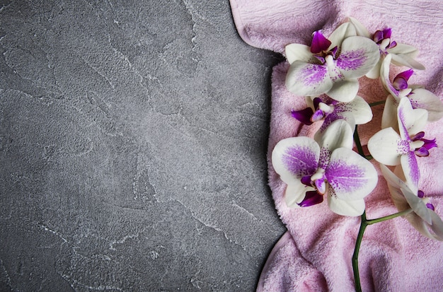 Toalla de masaje y flores de orquideas.