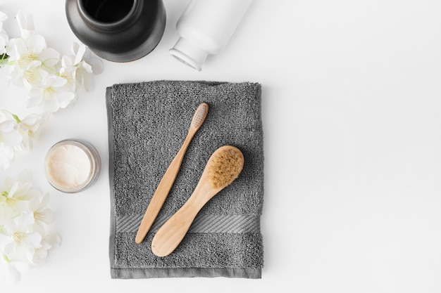 Toalla negra cepillo; crema hidratante; flores y recipiente sobre fondo blanco.