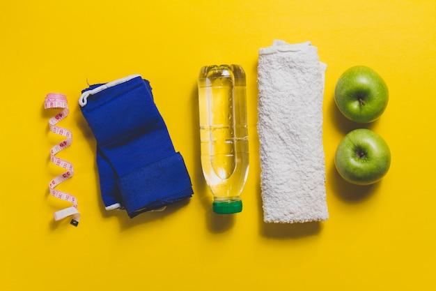 Toalla con otros accesorios de deporte sobre superficie amarilla Foto gratis