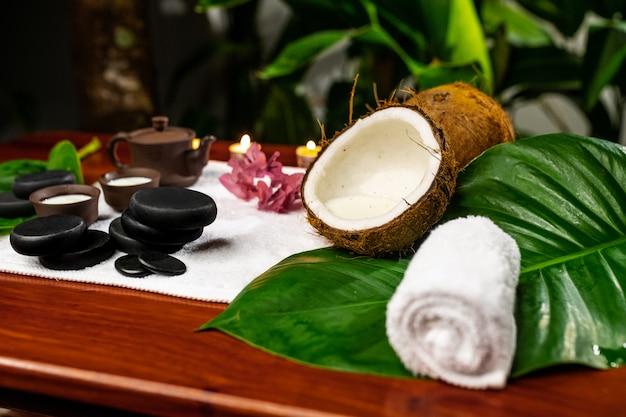 Una toalla en la que hay una tetera de arcilla y tazas para bebidas con leche, piedras para la terapia con piedras, velas, una flor de mangolia y una toalla retorcida sobre una mesa de madera.