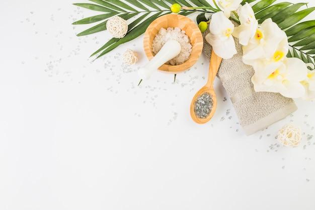 Toalla; sal del himalaya; flores falsas y hojas sobre fondo blanco