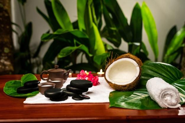 Una toalla con una tetera de arcilla y tazas para bebidas con leche, piedras para terapia con piedras, velas, una flor de mangolia y una toalla retorcida