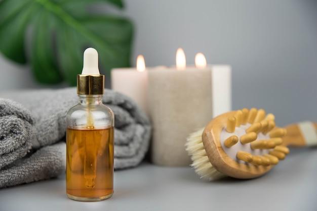 Toalla con velas aromáticas, botella con aceites esenciales orgánicos naturales y cepillo de masaje.