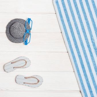 Toalla y zapatillas de playa con gorro y gafas de juguete.