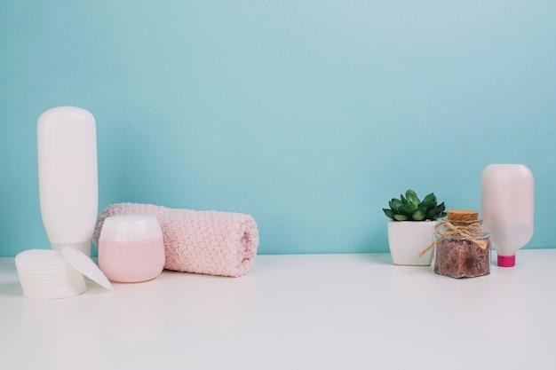 Toallas y almohadillas de algodón cerca de botellas de cosméticos