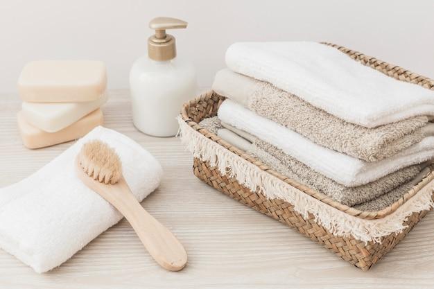 Toallas apiladas; cepillo; botella de jabón y cosmética en superficie de madera.