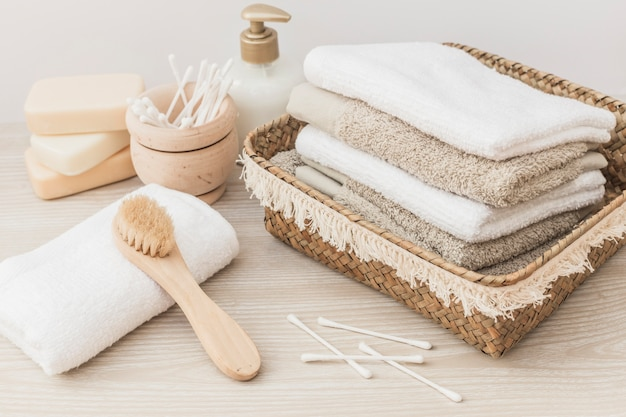 Toallas apiladas; cepillo; jabón; hisopo de algodón y botella cosmética sobre fondo de madera