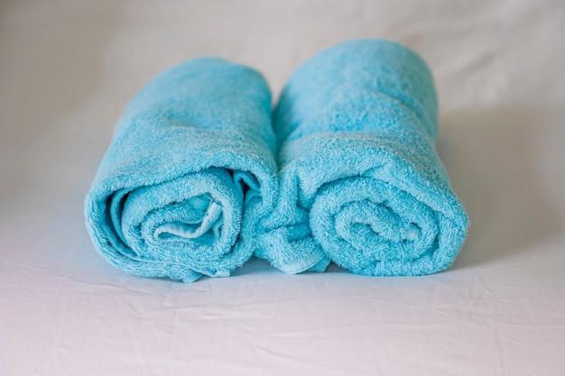 Toallas azules sobre cama blanca