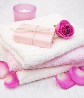 Toallas de baño y jabón con rosas rosadas.