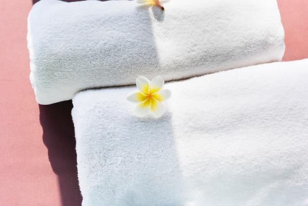 Toallas blancas decoradas con flores de plumeria