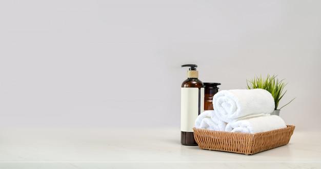 Toallas en cesta y accesorio de spa en mesa mable.