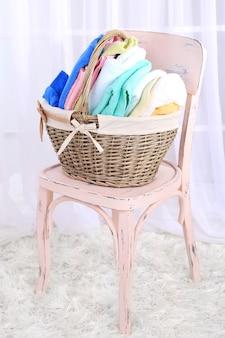 Toallas de colores en el canasto en una silla, en el interior de una casa