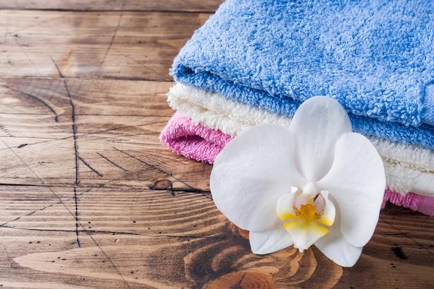 Toallas de colores y una flor de orquídea blanca.