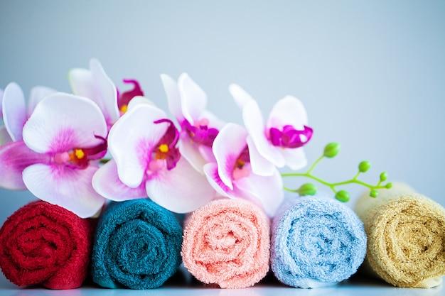 Toallas de colores y orquídeas en mesa blanca con espacio de copia en el baño.