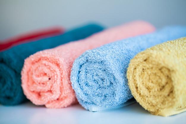 Toallas de colores sobre la mesa blanca con espacio de copia en el fondo de la sala de baño.
