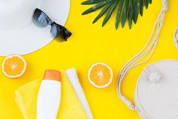 Toallas, hoja de palma, crema de protección solar, bolso, gorro, gafas de sol y naranja.