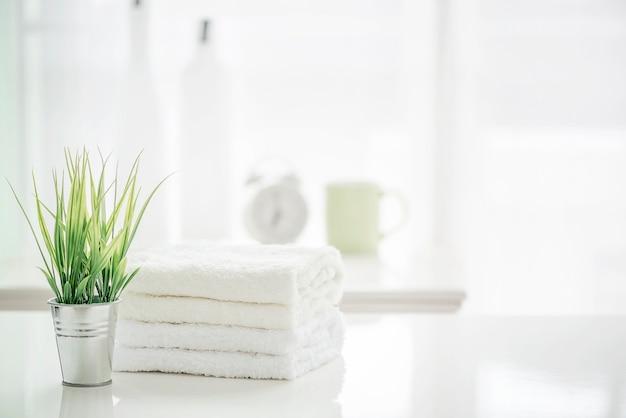Toallas en la mesa blanca con espacio de copia en el fondo de baño borrosa